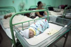 A new born baby rests beside his mother Dailyn Fleite (L), 29, at the Ana Betancourt de Mora Hospital in Camaguey, Cuba, June 19, 2015. The World Health Organization on Tuesday declared Cuba the first country in the world to eliminate the transmission of HIV and syphilis from mother to child. Picture taken June 19, 2015. REUTERS/Alexandre Meneghini